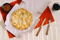 午饭时间,在一个开放箱子的比萨在桌上 库存照片