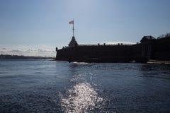 午间太阳在内娃河的水中反射了堡垒的墙壁的背景的 圣彼德堡 俄国 免版税库存图片