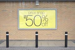 半价格在砖墙黄色外部商店商店商城的销售标志 图库摄影