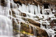 半冻五颜六色的Tupavica瀑布关闭和被日光照射了红色岩石和黄色草 库存图片