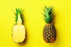 半切片新鲜的菠萝和整个果子在黄色背景 顶视图 复制空间 明亮的菠萝样式为 免版税库存照片