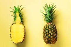 半切片新鲜的菠萝和整个果子在黄色背景 顶视图 复制空间 明亮的菠萝样式为 免版税库存图片