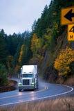 半卡车在有风秋天高速公路轮的雨中 免版税库存照片