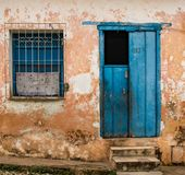 半开放蓝色门加上与花格的窗口在被撕碎的黄色wa 库存照片