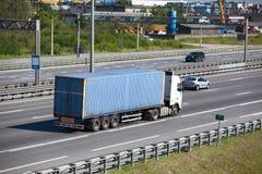 半拖车背面图有驾驶在高速公路的蓝色容器的 图库摄影