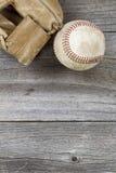 半新棒球和被风化的露指手套在老木头 库存图片