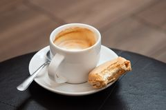 半满的杯子与金属匙子的浓咖啡macchiato和一半在茶碟的被吃的香草macaron 黑皮革桌 免版税图库摄影