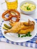 半烤鸡、啤酒、椒盐脆饼和土豆沙拉 库存照片