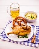 半烤鸡、啤酒、椒盐脆饼和土豆沙拉 库存图片