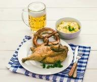半烤鸡、啤酒、椒盐脆饼和土豆沙拉 免版税库存图片