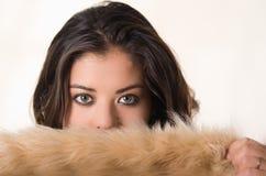 半特写有吸引力的深色的饰面照相机的覆盖物她的与棕色毛皮衣物,白色演播室背景的面孔 库存图片