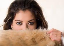 半特写有吸引力的深色的饰面照相机的覆盖物她的与棕色毛皮衣物,白色演播室背景的面孔 免版税图库摄影
