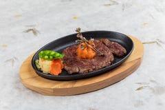 半生半熟wagyu牛排顶部与剁碎在热板和木板材的红萝卜服务用在washi的土豆沙拉 免版税库存照片