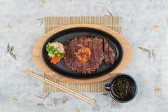 半生半熟wagyu牛排顶部顶视图与剁碎在热板和木板材的红萝卜服务用土豆沙拉, ponzu调味汁 库存照片