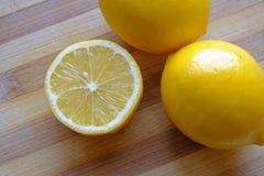 半的柠檬和两个整个柠檬冠上 库存照片