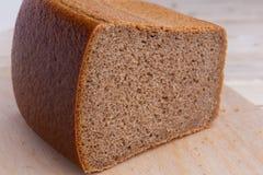半砖布朗酿造了从黑麦面粉的面包,在木书桌上 免版税库存图片