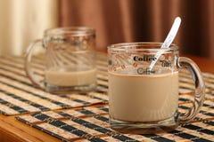 半空和充分的透明玻璃杯子用咖啡和牛奶在一个竹碗碟衬垫 库存照片