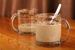 半空和充分的透明玻璃杯子用咖啡和牛奶在一张木桌上 库存图片