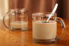 半空和充分的透明玻璃杯子用咖啡和牛奶在一张木桌上 免版税库存照片