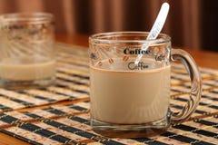 半空和充分的透明玻璃杯子用咖啡和牛奶在一张竹席子在咖啡馆 免版税库存图片