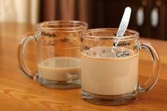 半空和充分的透明玻璃杯子用咖啡和牛奶在桌上 免版税图库摄影