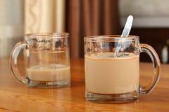 半空和充分的透明玻璃杯子用咖啡和牛奶在桌上 免版税库存照片