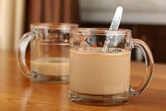 半空和充分的透明玻璃杯子用咖啡和牛奶在桌上 免版税库存图片