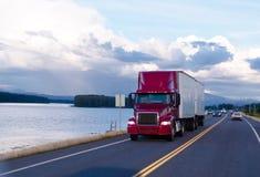 半红色卡车和两辆拖车在晚上路 库存照片