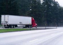 半红色在宽高速公路的卡车拖车有树的 免版税库存照片
