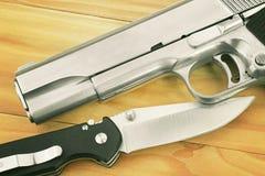 半自动手枪和作战刀子在木背景 免版税库存图片