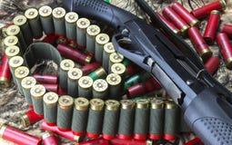 半自动猎枪、12个口径猎枪红色和绿色弹药筒弹药筒在子弹带和股票在伪装背景 免版税库存照片