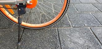 半自行车和黑立场橙色轮子在黑或灰色粗砺的地板上与拷贝空间 免版税库存图片