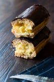 半黑暗的木表面上的裁减奶油被填装的巧克力饼 免版税图库摄影