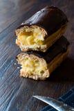半黑暗的木表面上的裁减奶油被填装的巧克力饼 库存图片