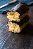 半黑暗的木表面上的裁减奶油被填装的巧克力饼 库存照片