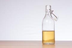 半满的开放玻璃杠杆瓶在桌上的啤酒 免版税库存图片