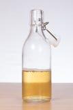 半满,被打开的玻璃瓶在桌上的啤酒 库存图片