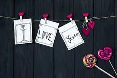 华伦泰与一个消息`我爱你`绳子和桃红色别针的` s卡片有焦糖心脏的,垂悬在纹理背景 库存图片