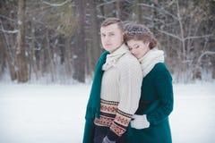 华伦泰与绿色羊毛毯子的夫妇覆盖物在冬天森林里 图库摄影