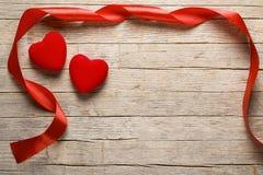 华伦泰在木桌上的` s心脏与红色丝带 免版税库存照片