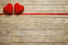 华伦泰在木桌上的` s心脏与红色丝带 免版税图库摄影