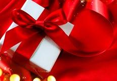 华伦泰在红色丝绸背景的礼物盒 免版税库存图片