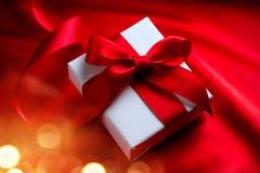 华伦泰在红色丝绸背景的礼物盒 免版税库存照片