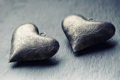 华伦泰在花岗岩板的金属心脏 与装饰品的华伦泰的两银色心脏 爱华伦泰和婚礼之日的心脏 免版税库存图片
