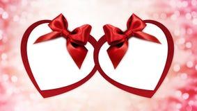 华伦泰心脏形状与被隔绝的红色丝带弓的礼品券  免版税图库摄影