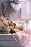 华伦泰或陶瓷心脏、珍珠、桃红色鞋带和纸纸卷婚礼之日静物画在葡萄酒减速火箭的木箱 库存图片