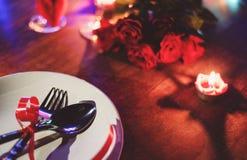 华伦泰晚餐浪漫爱概念/用在白色板材和玫瑰的叉子匙子装饰的浪漫桌设置 免版税库存图片