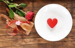 华伦泰晚餐浪漫爱烹调概念/红心在白色板材浪漫桌设置的食物和爱 库存照片