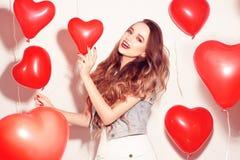华伦泰有红色气球的秀丽女孩笑,在白色背景的 美丽的愉快的妇女年轻人 妇女天 节日晚会 库存照片