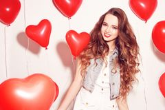 华伦泰有红色气球的秀丽女孩笑,在白色背景的 美丽的愉快的妇女年轻人 妇女天 节日晚会 免版税库存图片